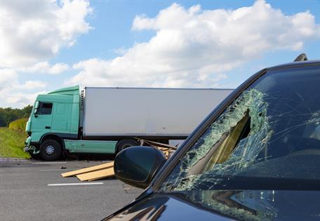 Image of a blue semi truck on the side of the road and a sedan with a broken windshield in the middle of the road